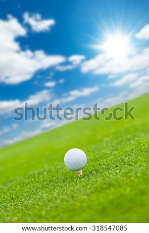 Golf ball on the green lawn with cloudy sky