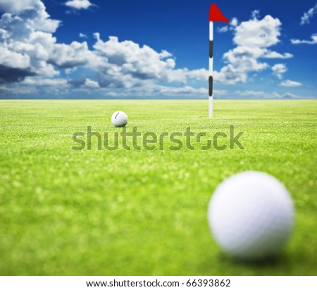 Golf ball on the green ready to be putt into the hole - very shallow depth of field - stock photo