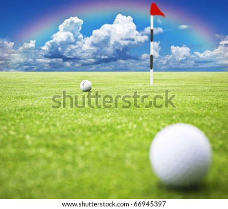 Golf ball on the green ready to be putt into the hole with a rainbow in the background - very shallow depth of field - stock photo
