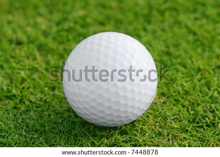 Golf ball on the green. Shallow DOF, focus on ball.