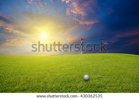Golf ball on the lawn and blurred sky-clouds and sunlight