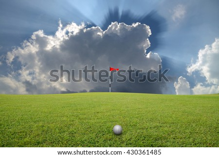 Golf ball on the lawn and blurred sky-clouds background. - stock photo