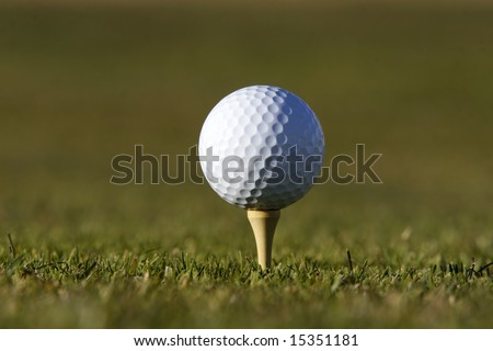 Golf ball on the tee with green background - stock photo