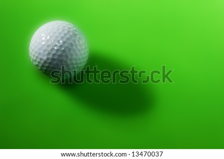 golf ball over light green background with long shadow - stock photo
