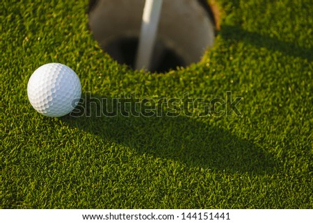 Golf ball putted inches from the cup - stock photo