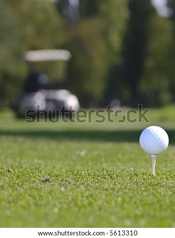 Golf ball set against green grass with cart in the background - stock photo