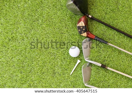 Golf ball, tee and golf clubs on green grass background. - stock photo