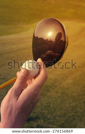 golf ball, tee and grass with reflection of the player - stock photo