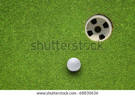 Golf ball very close to the hole - stock photo
