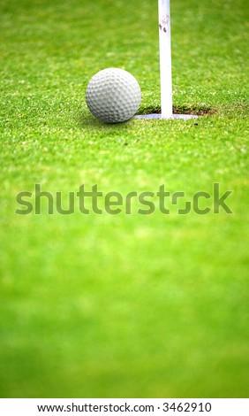 golf ball very near a flag hole - stock photo