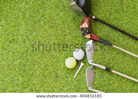 Golf ball, white tee and old golf clubs on the green grass background.Outdoor sport concept. - stock photo