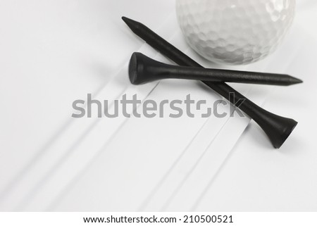 Golf ball with black tees on white pleats - stock photo