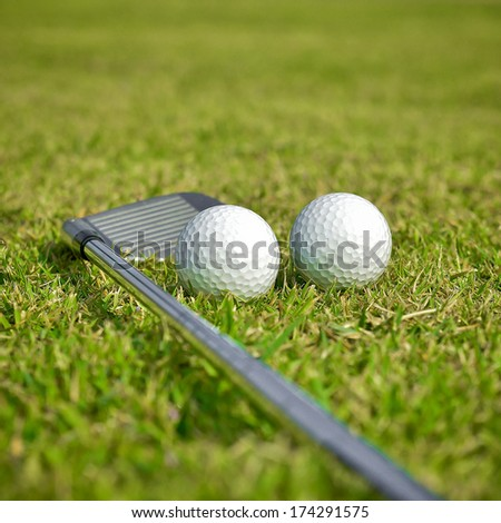 Golf ball with club on green grass