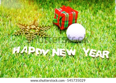 Golf ball with gift for new year and Happy New Year lettering on green grass.