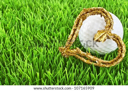 GOlf ball with golden heart on the fairway - stock photo