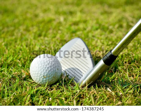 Golf ball with golf club on green grass  - stock photo