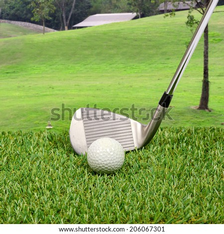 Golf ball with golf club with grass hill background - stock photo