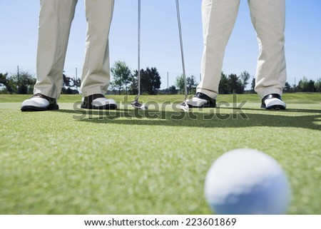 Golf ball with golfers in background - stock photo