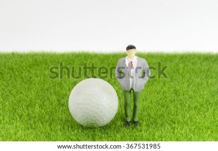 golf ball with mini toy businessman on a grass - stock photo