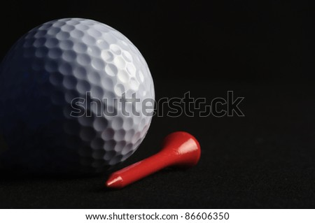 Golf ball with red tee on black background - stock photo