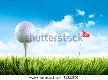 Golf ball with tee in the grass against blue sky - stock photo