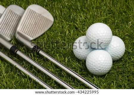 Golf balls and golf clubs with steel shaft on grass. - stock photo