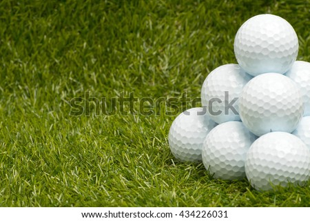 Golf balls arranged in pyramid form on green grass. Room for text on left. - stock photo