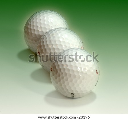 Golf balls on a green background. - stock photo