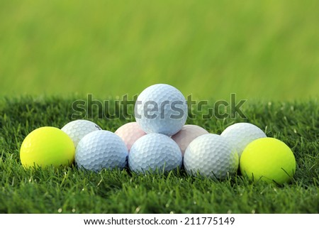 Golf balls on green grass background - stock photo