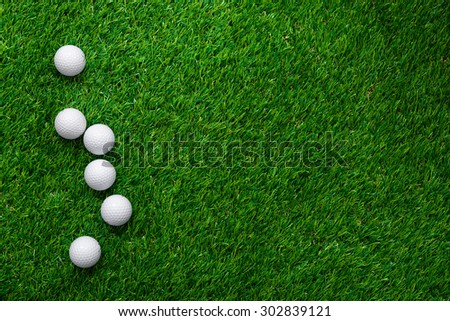 Golf balls on green grass in golf course - stock photo