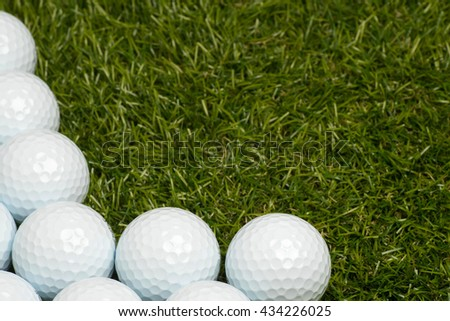 Golf balls on green grass on the left. Room for text on the right. - stock photo