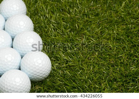 Golf balls on green grass on the left side. Room for text on the right. - stock photo