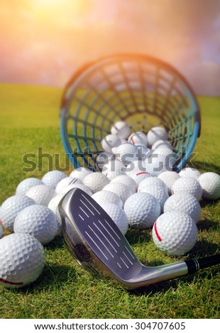 Golf balls pouring out of basket onto grass - stock photo