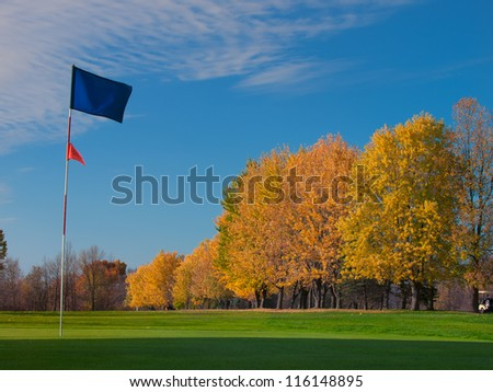 Golf blue flag on green in fall - stock photo