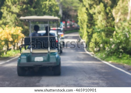 Golf cart driving on the road.