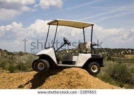 Golf cart high centered on a dirt mound - stock photo