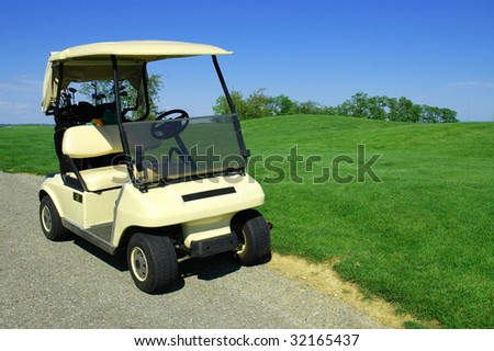 Golf cart on path, grass blue sky