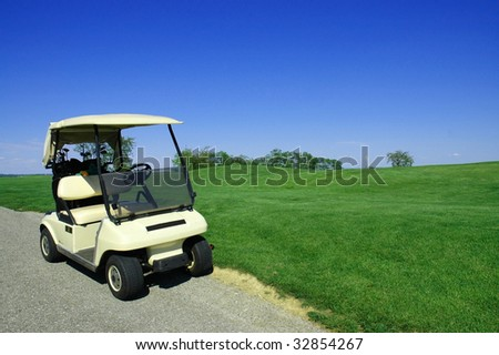 Golf cart on path, pretty green grass and blue sky background room for copy space
