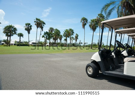 Golf carts on side of golf course. - stock photo