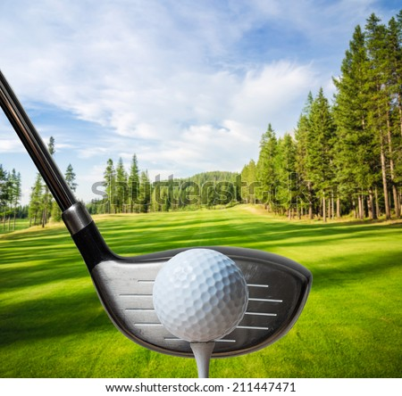 Golf club about to hit a golf ball on the course - stock photo