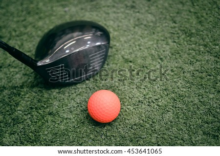 Golf club and ball, grass background. Closeup view shot