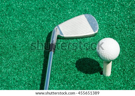 golf club and ball on a stand with artificial turf