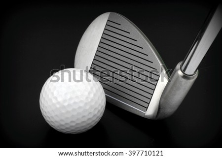 Golf club and ball on black background - stock photo