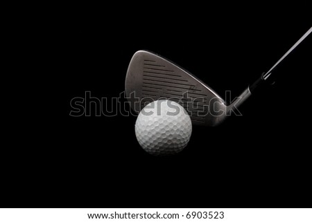 Golf club and ball on black background
