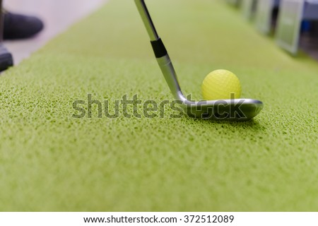 Golf club and ball on green indoor grass background. Closeup photo - stock photo