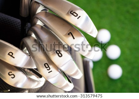 Golf club and blurry golf ball in the green grass. - stock photo