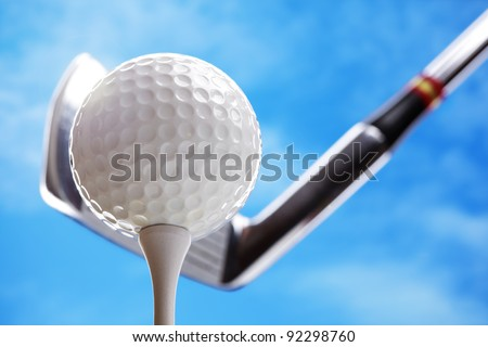 Golf club and golf ball about to tee off against a blue sky - stock photo