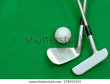 Golf club and golf ball on green felt background. Copy space for your message on the green felt background. Putter club and ball are positioned to the right of the image, room for text on the left - stock photo