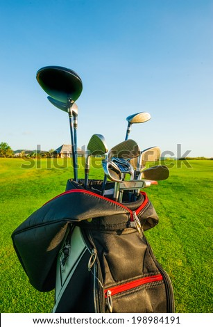 Golf club. Bag with golf clubs Green golf field and ball in grass - stock photo