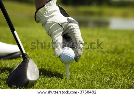 Golf club: golfer arranging the ball on the tee - stock photo